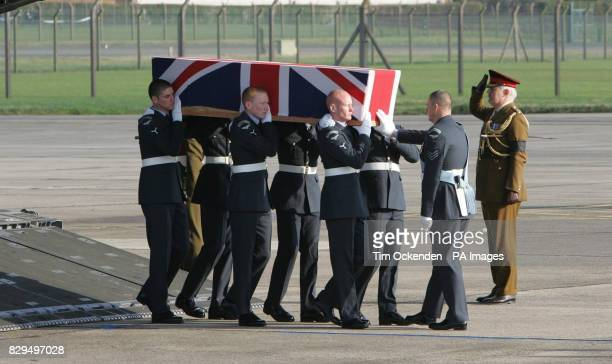 Service personnel carry the coffin of Flt Lt Andrew Smith as it is returned to the UK He was one of ten servicemen killed when the C130 Hercules...