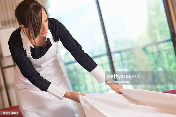 Service professional making bed in hotel room