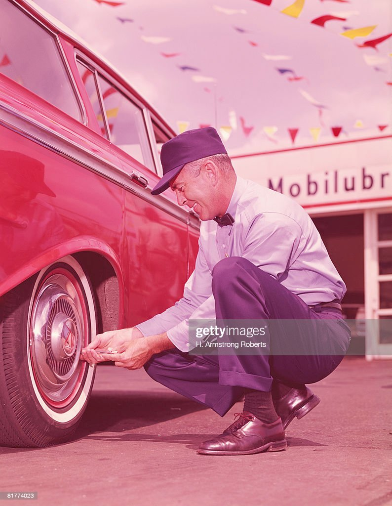 Service station attendant checking air pressure in tyres of car. (Photo by H. Armstrong Roberts/Retrofile/Getty Images) : Stock Photo