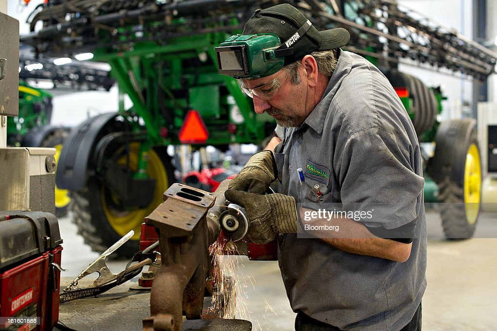 Service technician George Clayton grinds temporary spot welds while working on an exhaust manifold for a customer's John Deere tractor at Klein Equipment, a John Deere dealership, in Galesburg, Illinois, U.S., on Tuesday, Feb. 12, 2013. Deere & Co., the world's largest maker of agricultural equipment, is scheduled to release quarterly earnings on Feb. 13. Photographer: Daniel Acker/Bloomberg via Getty Images