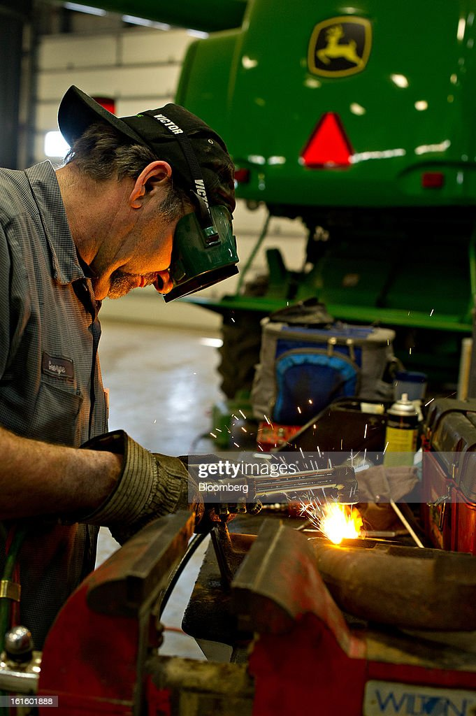 Service technician George Clayton uses a torch to heat a broken bolt while working on an exhaust manifold for a customer's John Deere tractor at Klein Equipment, a John Deere dealership, in Galesburg, Illinois, U.S., on Tuesday, Feb. 12, 2013. Deere & Co., the world's largest maker of agricultural equipment, is scheduled to release quarterly earnings on Feb. 13. Photographer: Daniel Acker/Bloomberg via Getty Images