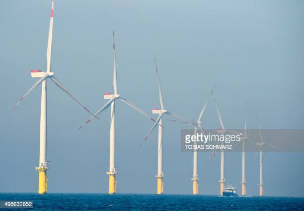 A service vessel passes by wind turbines of the German offshore wind farm 'Amrum Bank West' owned by German energy company EON near the Heligoland...
