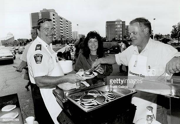 Service with a smile Peel police Sergeant Bill Hughes left is all smiles as he and Detective Doug Wilson ready a plate of pancakes for Carmen...