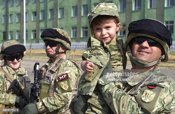 Serviceman Andro Khchukhidze holds his threeyear old daughter Tinatin during a farewell ceremony at the Vaziani military base outside Tbilisi on...