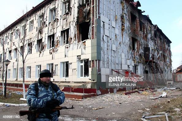 A serviceman guards near a school building damaged during fighting between militants and police in Grozny on December 5 2014 Islamist insurgents...