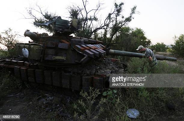 A serviceman holds position next to a destroyed tank on the position of Ukrainian forces in the Lugansk region on August 26 2015Ties between the EU...