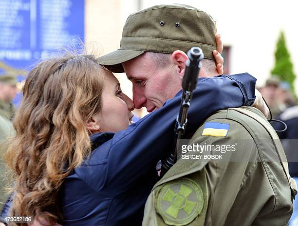 A serviceman of Ukrainian National Guard kisses his girlfriend after a ceremony of oath at the Academy of the National Guard in Kharkiv on May 16...