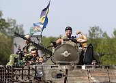A serviceman postures on the APC located of the Ukrainian troops in Donetsk region on August 9 2014 Fighting with proRussian separatists in eastern...