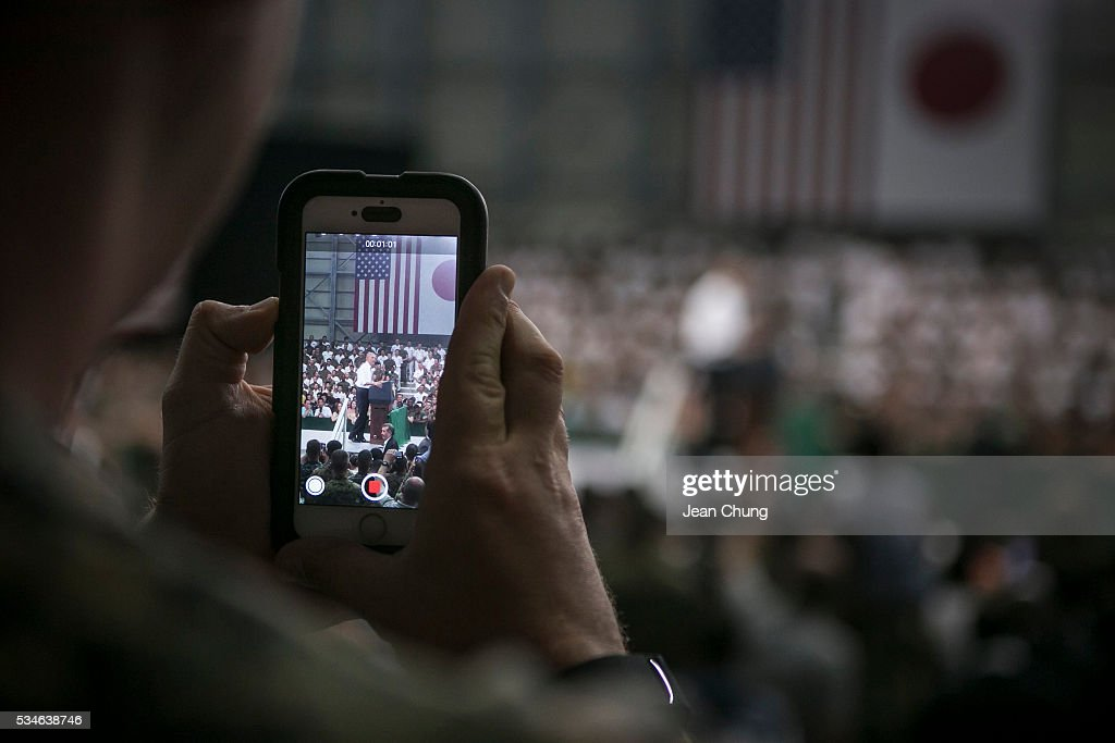 A U.S. serviceman (L) takes a snapshot of U.S. President Barack Obama (R) during his speech at the Marine Corps Air Station Iwakuni (MCAS Iwakuni) on May 27, 2016 in Iwakuni, Japan. President Barack Obama flew in to the MCAS Iwakuni on Air Force One, and visited the troops before visiting Hiroshima.