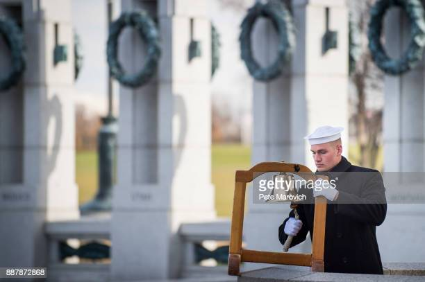 A serviceman with the US Navy ring a ships bell to mark the time of the Japanese attack on Pearl Harbor during the Friends of the National World War...