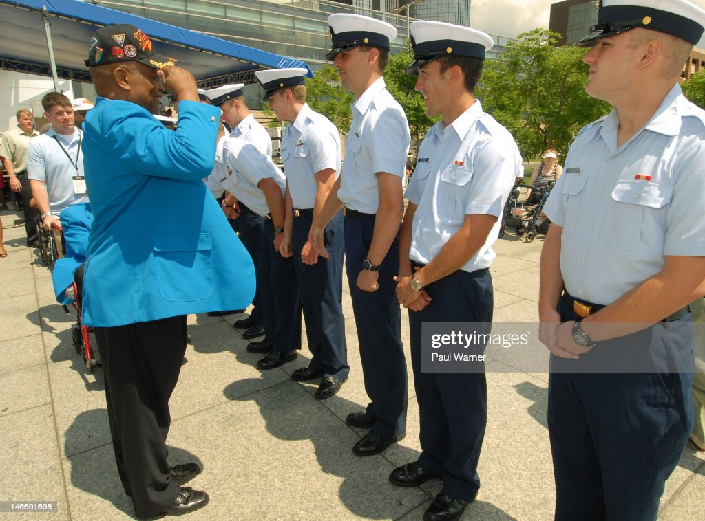 Servicemen (R) greet members of the Tuskegee Airmen at the opening ceremony of the 2012 Detroit River Days Festival at the Detroit RiverWalk on June 22, 2012 in Detroit, Michigan.