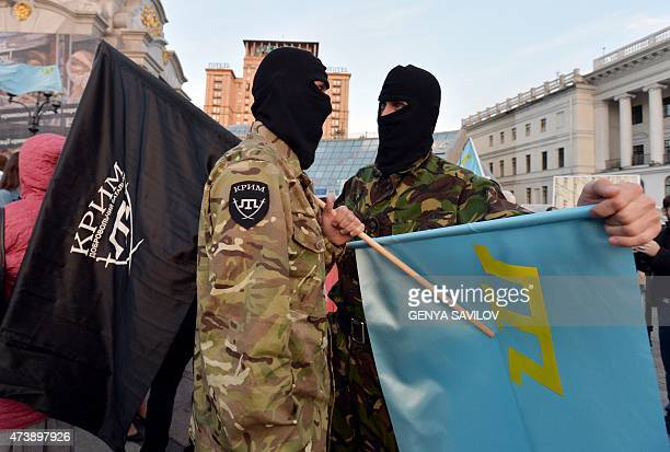 Servicemen hold flags of the Crimea Battalion and the National flag of Crimean Tatars as people particpate in a rally on Independence square in Kiev...