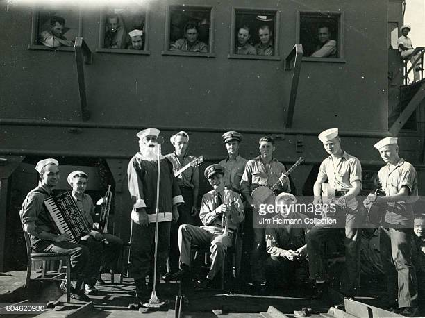 Servicemen playing accordion trumpet banjo and guitar perform with man dressed as Santa Claus Other service men watch from windows of train stopped...