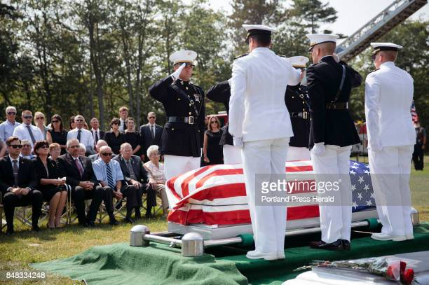 Servicemen salute after they lay Ben Cross' casket down to rest at Riverside Cemetery Cross was one of the Marines killed on Aug 5 when their MV22...