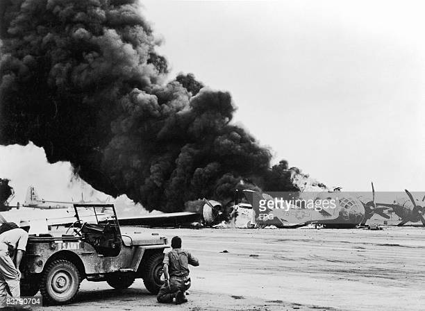 US servicemen shelter behind a jeep to avoid exploding ammunition as a B29 Superfortress of the 21st Bomber Command crashlands on Iwo Jima colliding...
