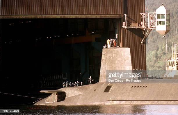 Servicemen stand aboard the final Trident nuclear submarine HMS Vengeance as it edges its way into the naval base at Coulport Scotland Coulport is...