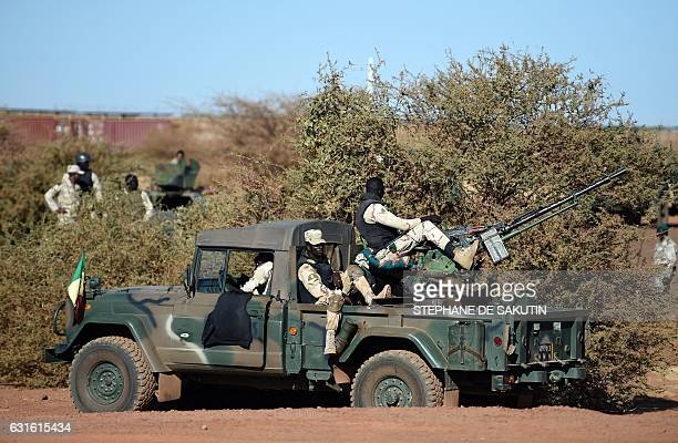servicemen stand guard on a military vehicle as part of a visit of French President to the troops of France's Barkhane counterterrorism operation in...