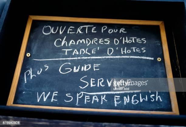 ServiceSchild in einer AltstadtKneipe von RochefortenTerre in der Bretagne mit der einladenden Aufschrift fuer Touristen Speak English hier wird auch...