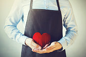 Servicing man in apron holding open armed heart with hands - customer relationship and service minded business concept.