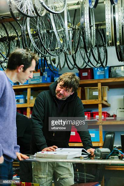 Serving a customer, bicycle shop, looking at a catalogue