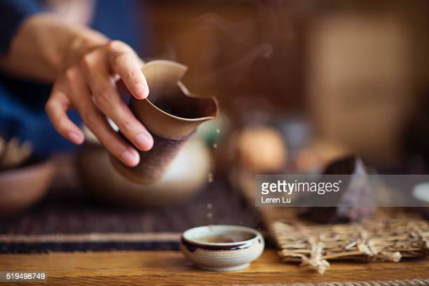 Serving Chinese tea into ceramic tea cups