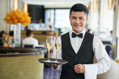 Portrait of smiling Vietnamese waiter serving drinks in restaurant