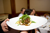 Waiter serving tarragon crusted beef tenderloin, gnocchi,mushrooms,artichokes, canon 1Ds mark III