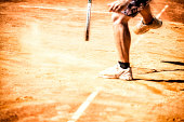 Tennis player in action on a clay court.