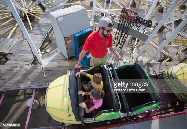 Serxhio Dushi secures Hannah Sloma and her brother Levi of West Paris into a car as the prepare to ride the Galaxi Coaster in Old Orchard Beach on...