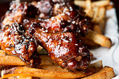 Teriyaki Glazed Chicken Wing Appetizer over French Fries.