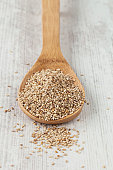 Bunch of fresh sesame on a wooden spoon