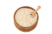 Sesame seeds in wooden bowl isolated on white
