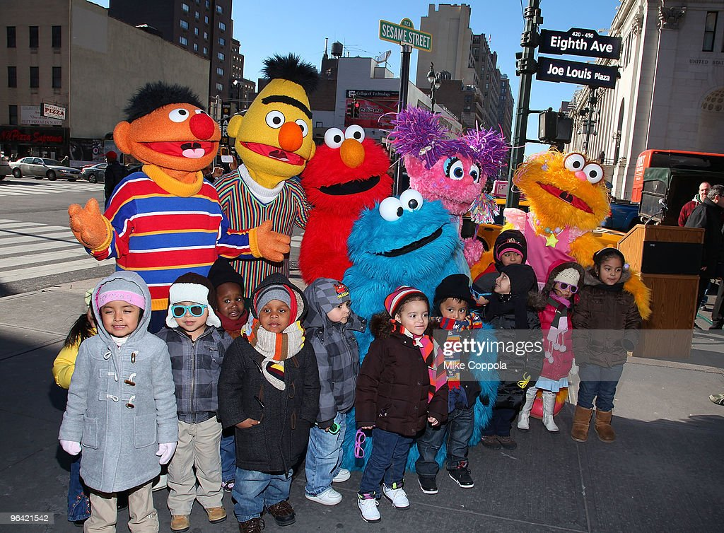 Sesame Street characters Ernie Burt Elmo Cookie Monster Abby Cadabby and Zoe pose with children from the Garden of Dreams Foundation at the temporary...