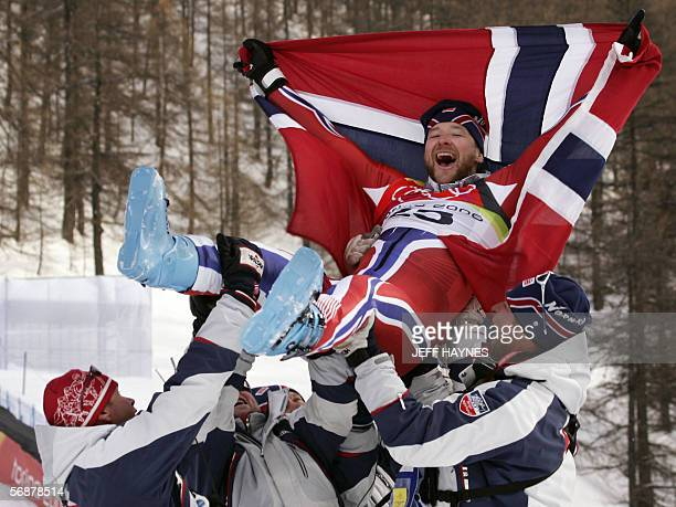 Kjetil Andre Aamodt from Norway is carried by teammates 18 February following the Men's SuperG in Sestriere Borgota Italy Aamodt who stopped the...