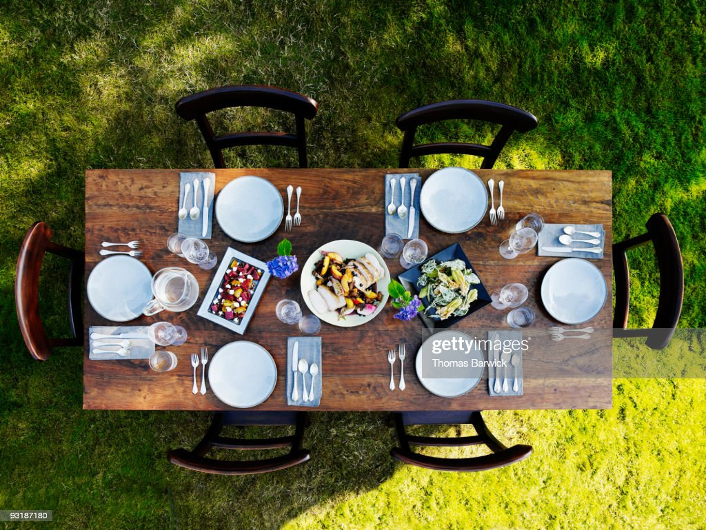 Set dinner table outside on grass lawn : Stock Photo