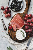 Assorted italian antipasti snacks for a dinner with wine or party on wooden cutting board. Red grapes, fresh camambert cheese, prosciutto and black olives. Top view, desaturated colors