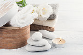 Set of bathroom accessory on wooden background: pebbles, towels, candle