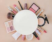 Beauty products on a beige background. Eyeliner, blushes, concealer, foundation, lipsticks, nail polishes, mascara.