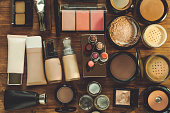 Set of decorative cosmetic. Powders, concealer, eye shadow blush, foundations. Wooden background.