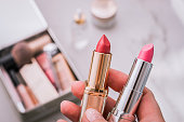 A person holds two lipsticks. Beauty products blurred background. Top view.