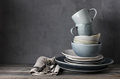 Stack of grey crockery and silverware on rustic wooden table against shabby gray wall. Various plates, dish, bowls and mugs.