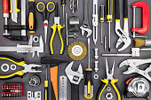set of hand various work tools on grey background top view including different kinds of wrenches, pliers, clamps, calipers and other