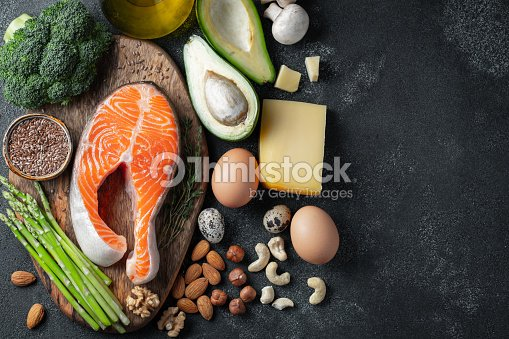 A set of healthy food for keto diet on a dark background. Fresh raw salmon steak with flax seeds, broccoli, avocado, chicken eggs, nuts and asparagus on a wooden Board. Top view with copy space : Stock Photo