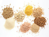 Set of heap various grains and cereals - raw green buckwheat, semolina, oat flakes, millet, brown rice, buckwheat or kasha,quinoa, and red rice.Isolated on white with clipping path.Top view.Copy space