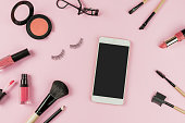 Set of make up brushes and cosmetics on pink background with smart phone and copy space, Top view