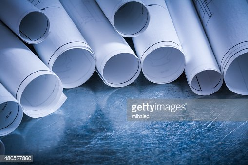 Set of rolled up white construction drawings on scratched silver : Stockfoto
