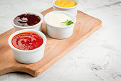 Classic set of sauces in white saucers: American yellow mustard, ketchup, barbecue sauce, mayonnaise. On cutting board white stone concrete table close view, copy space