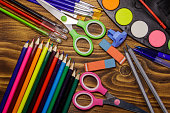Set of school stationery supplies. Colored pencils, watercolor paints, paintbrushes, pens, scissors, eraser, sharpener on wooden desk. Back to school concept