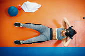Experienced personal trainer and attractive healthy woman exercising in gym and cross training facility. Woman is exercising strength training in order to keep her body in good shape.