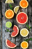 Set of sliced citrus fruits lemon, lime, orange, grapefruit with mint over wooden background. Top view.